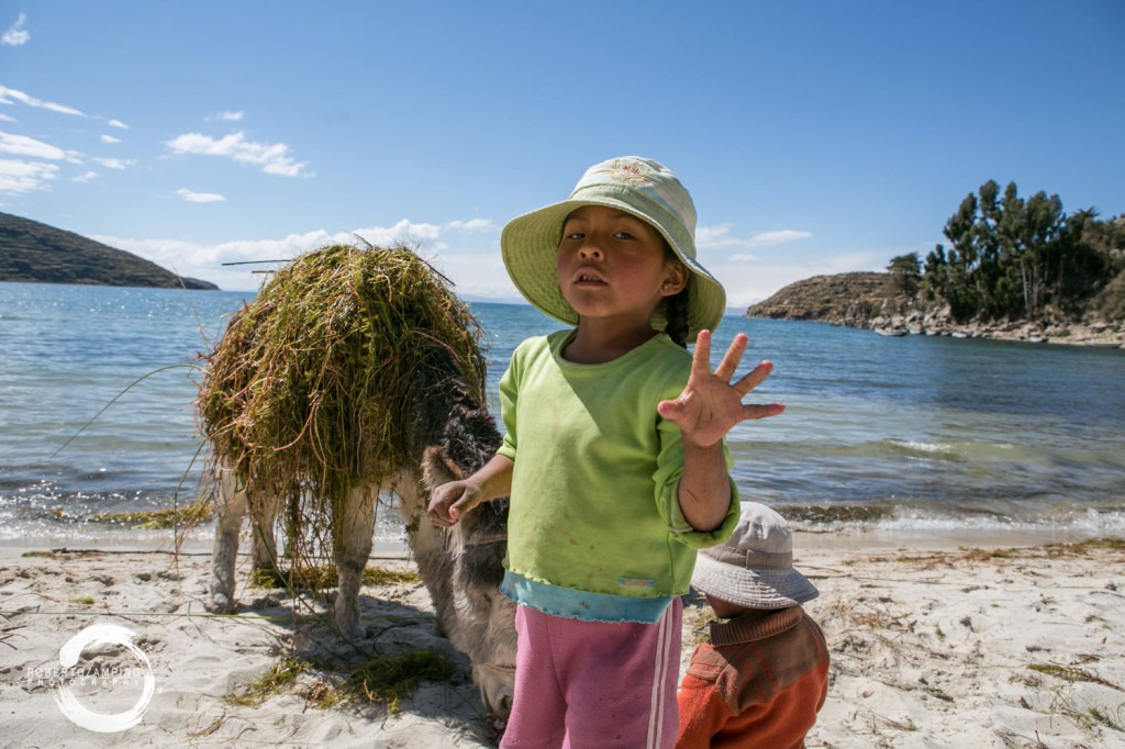""" you gring cannot understand!"" - children feeding a donkey in the isla del sol - the sun island - bolivia"